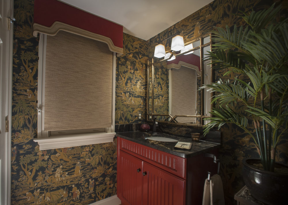 Asian inspired powder room with bamboo framed mirror, grass cloth window shade complemented by a custom pagoda-shaped valance, and scenic oriental wallpaper.