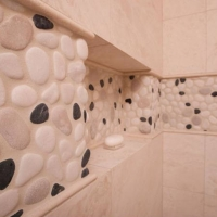 Shower wall tile with pebble accents.